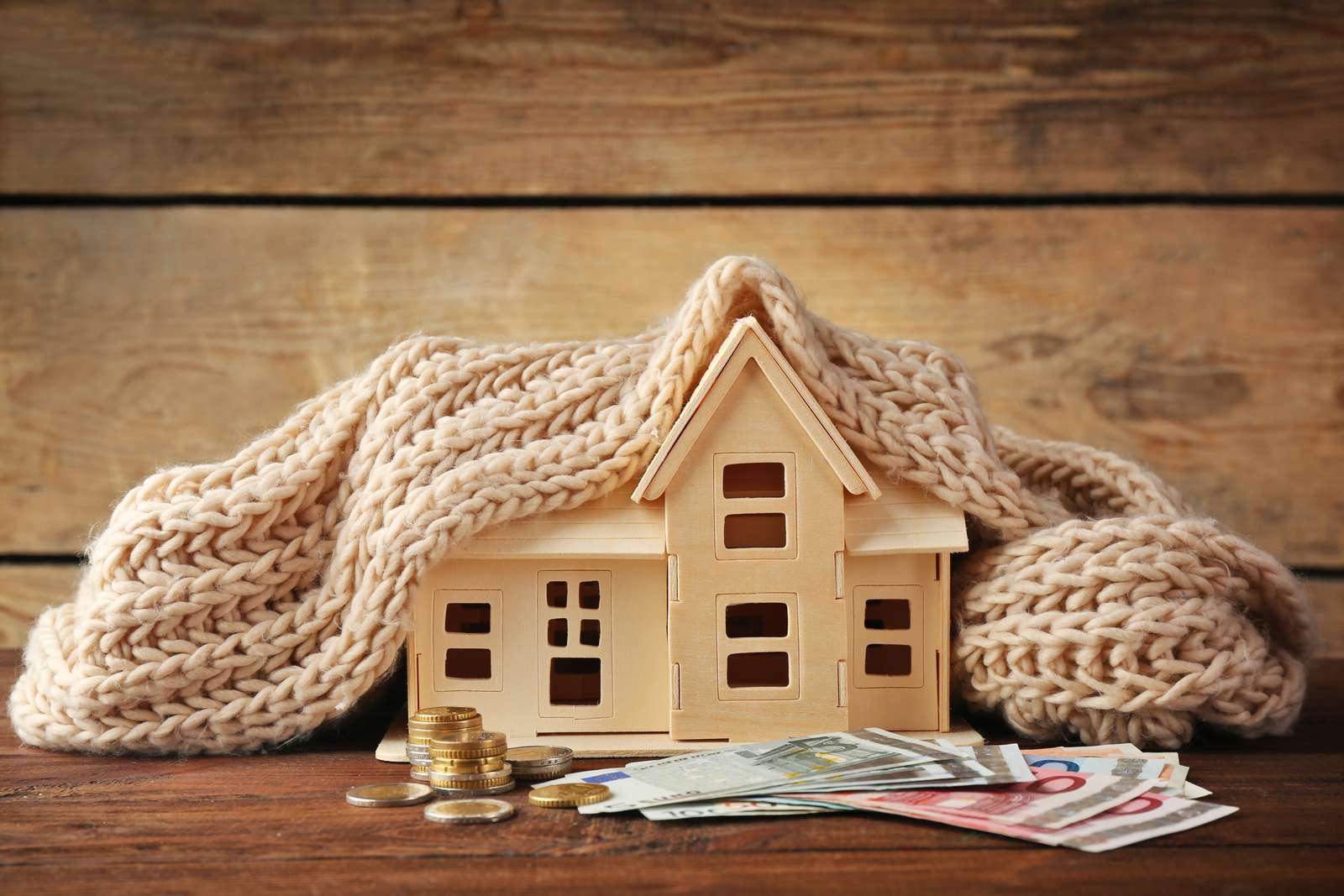 Plywood toy house with warm scarf and money on wooden background